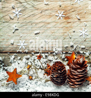 Pine cones, golden orange stars and snow in an Xmas background with snow flake decorations on textured old wooden - Stock Photo