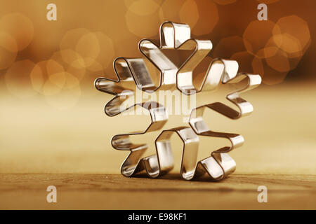 Snowflake Christmas background with a shiny aluminium cookie cutter standing upright on a sepia background with - Stock Photo