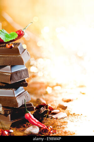 A tower of chocolate blocks covered in red hot chiliswith copyspace of bright lights for concepts related to chocolate - Stock Photo