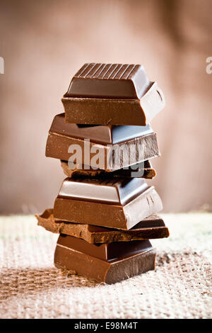 Tower composed of pieces of staple chocolate on a linen background for chocolate and cocoa concepts. - Stock Photo