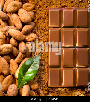 Chocolate piece from above, with powdered cocoa, a leaf and cacao beans - Stock Photo