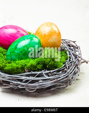 Three colourful marbled Easter eggs on green moss in a nest constructed of interwoven twigs - Stock Photo