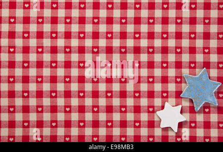 Background of two silver stars lying on colourful fresh red checked fabric with tiny hearts - Stock Photo
