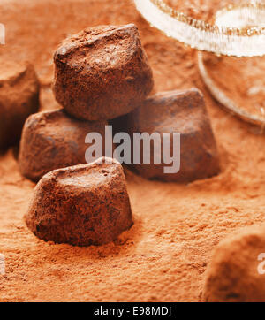 Handmade luxury chocolate bonbons sprinkled with, and lying in, cocoa powder with gold festive ribbon - Stock Photo