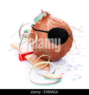 Coconut with an eye patch, confetti and a paper streamer. For little Pirates and caribbean and tropical concepts. - Stock Photo