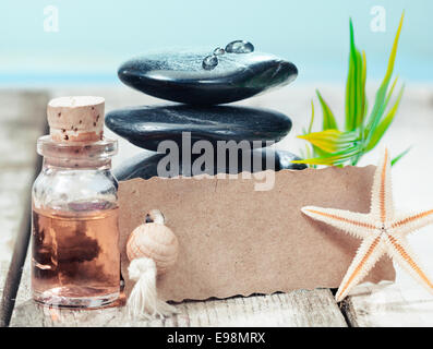 Beautiful serrated edged blank label leaning on a stack of black hot massage stones near the sea offering a gift - Stock Photo