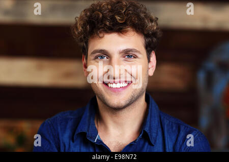 Portrait of a smiling handsome man with curly hair - Stock Photo