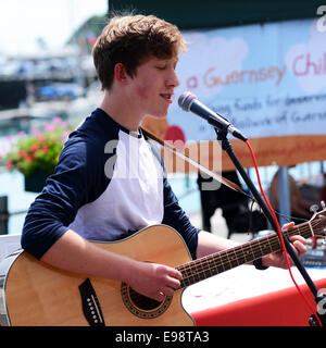 Youth playing a guitar and singing outdoors - Stock Photo