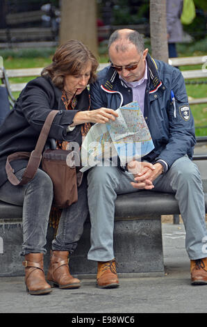 Tourists in Washington Square Park in Greenwich Village, New York City,  studying a map of the city. - Stock Photo