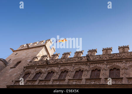 Valencian flag flying from a tower above the Silk Exchange building in Valencia, Spain. - Stock Photo