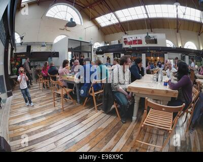 Families enjoying a lfamily day out with freshly made pizza and real ales in the renewed Market Hall in Altrincham - Stock Photo