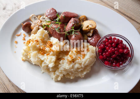 Close up on delicious dish of reindeer sausage, mushrooms, mashed potatoes and cranberry. Oslo, Ostlandet. Norway - Stock Photo