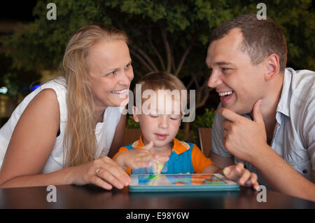 Happy family with tablet PC outdoor in the evening - Stock Photo