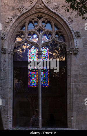 Ligh from a stained glass window shines through another window at the Silk exchange building, Valencia, Spain. - Stock Photo