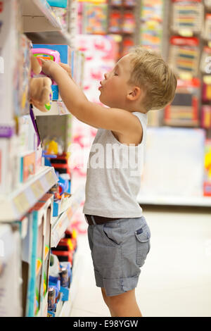 Boy choosing toy in the shop - Stock Photo