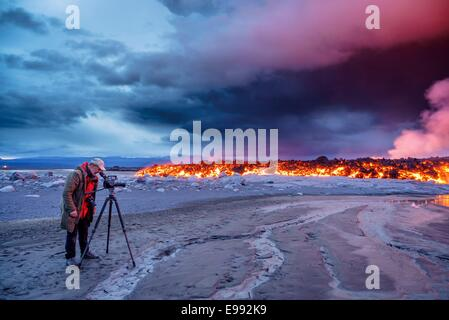 Photographer filming the volcano eruption at the Holuhraun Fissure, near the Bardarbunga Volcano, Iceland. - Stock Photo