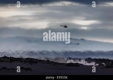 Helicopter flying over the volcano eruption at the Holuhruan Fissure, near the Bardarbunga Volcano, Iceland. - Stock Photo