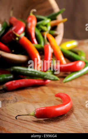 a composition of chillies on a wooden board - Stock Photo