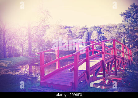 Vintage filtered picture of red bridge in garden. - Stock Photo