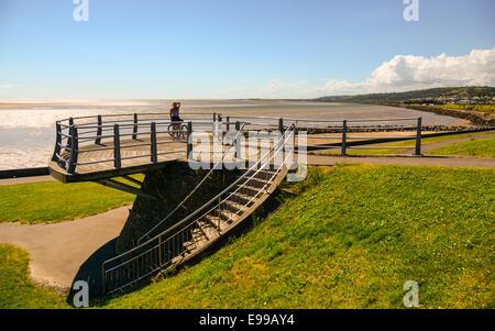 A woman cyclist looks out towards Burry Port from a viewing platform on the Millennium Coastal Path, Wales. - Stock Photo