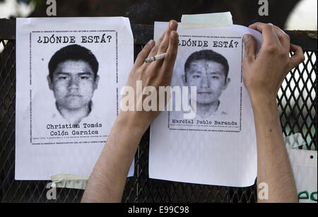 Buenos Aires, Argentina. 22nd Oct, 2014. A demonstrator pastes photos of missing students during a protest for the - Stock Photo