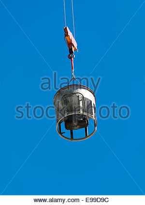 Detail of a construction site, a crane carries concrete to be dropped in the roof of a building. - Stock Photo