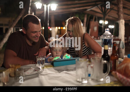 Parents and child with tablet PC in outdoor cafe - Stock Photo