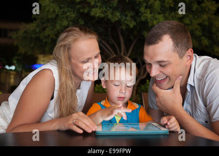 Family of three with pad in outdoor cafe - Stock Photo