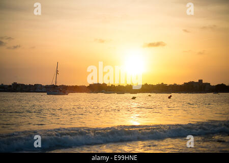 Sunset over the sea and city. Photograph from the beach. - Stock Photo