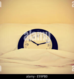 picture of a clock inside a bed, with a retro effect - Stock Photo