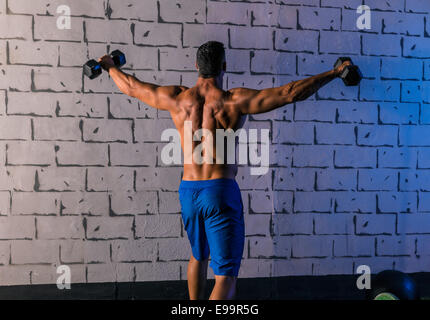 gym man rising hex dumbbells weightlifting rear view - Stock Photo