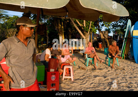 Beach of Kuta at sunset. Drinking beer. Bali. Kuta is a coastal town in the south of the island of Lombok in Indonesia. - Stock Photo