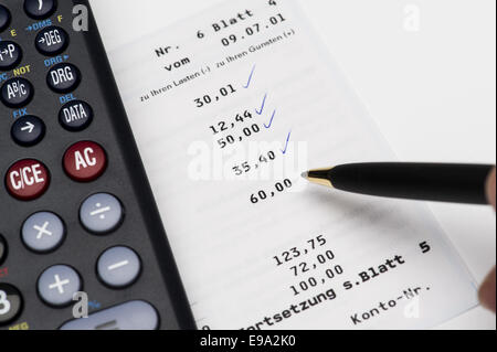 Calculator is located on a bank statement - Stock Photo