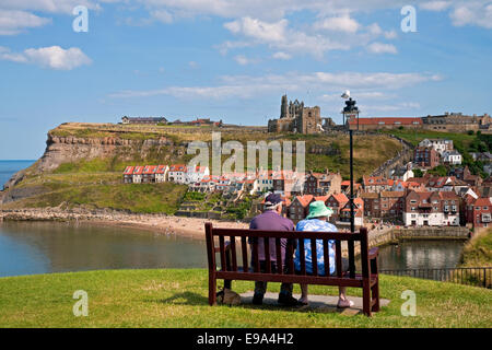 Two people old senior couple sitting on bench overlooking the Abbey and harbour in summer Whitby North Yorkshire England UK United Kingdom Britain Stock Photo