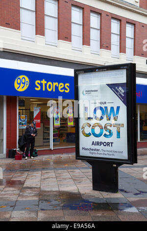 Low Cost Travel Poster, and Ninety Nine pence Stores in Town Centre as Warrington Borough Council propose to regenerate - Stock Photo