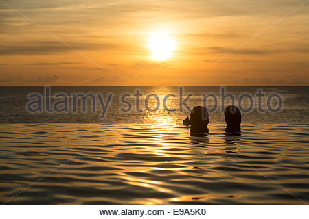 Silhouetted heads against infinity edge pool - Stock Photo