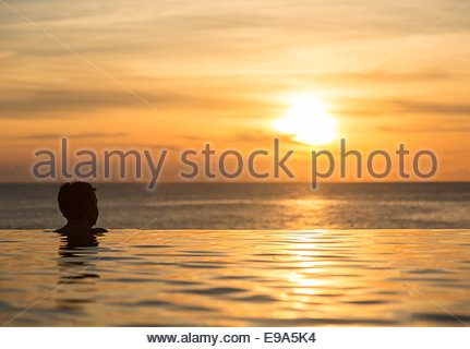 Silhouetted head against infinity edge pool - Stock Photo