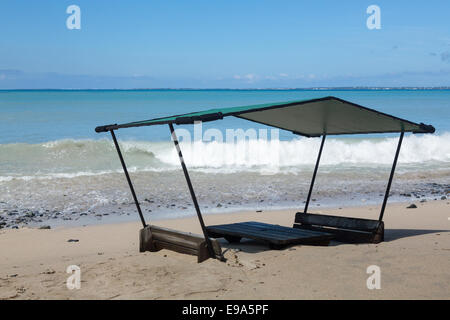 Seats and table on beach covered in sand - Stock Photo