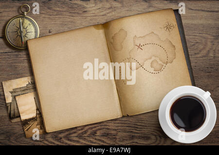Adventure and travel nautical theme. Diary with map and compass on wooden table. - Stock Photo