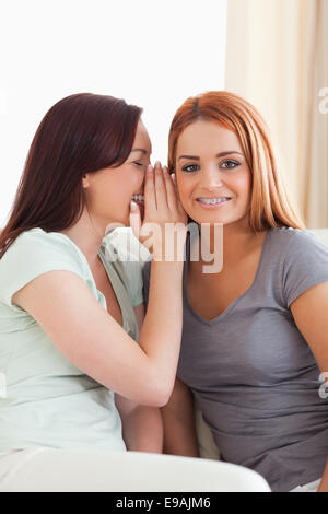 Cute woman being told a secret - Stock Photo