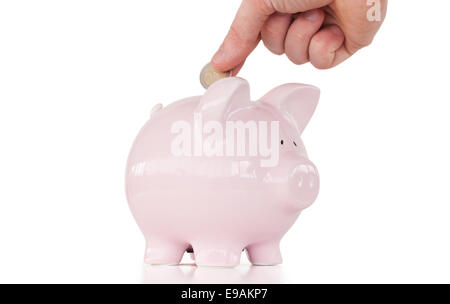Hand inserting a coin in a pink piggy bank - Stock Photo