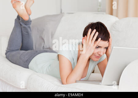 Unhappy woman using a laptop - Stock Photo