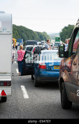 Traffic at standstill / not moving due to incident. Waiting drivers / passengers have left cars & vehicles to wonder - Stock Photo