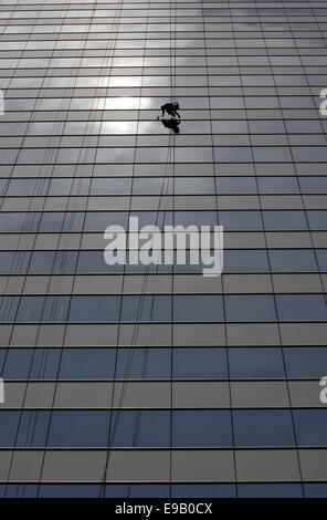 Window cleaner cleaning a window pane - Stock Photo