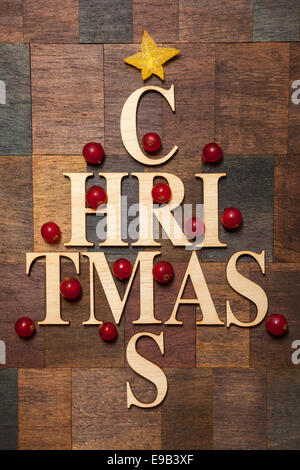 Wooden letters shaped tree forming the word ''christmas'' with redcurrants - Stock Photo