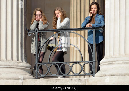 London, England, UK. Three girls looking over Trafalgar Square from the National Gallery - Stock Photo