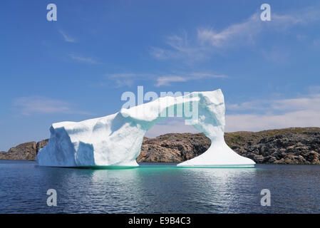 Iceberg in front of a rocky island near Twillinggate, Newfoundland and Labrador, Canada - Stock Photo