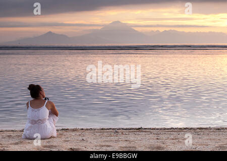 Woman sitting on sand beach watching sunset over sea, view of Bali from 'Gili Trawangan', 'Gili Island', Indonesia