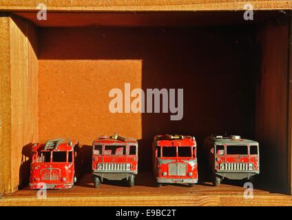 four Matchbox toy fire engines in a wooden box - Stock Photo
