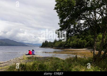 Two women sitting on the banks of Loch Linnhe, Lochaber, Highland, Scotland - Stock Photo